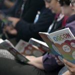 a photograph of an audience reading qgcon brochures